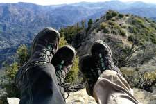 Two people wearing hiking boots sitting on mountain top