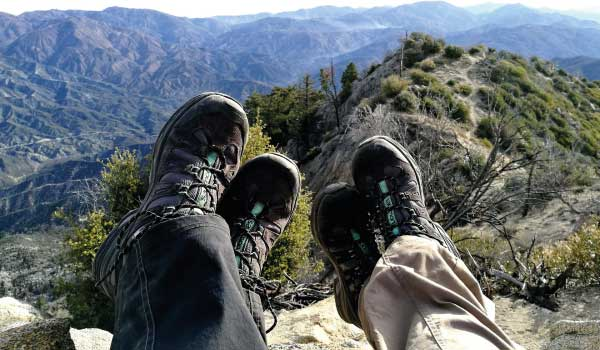 Two people wearing hiking boots sitting on the mountain top