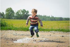 Young body jumping in puddle on dirt track