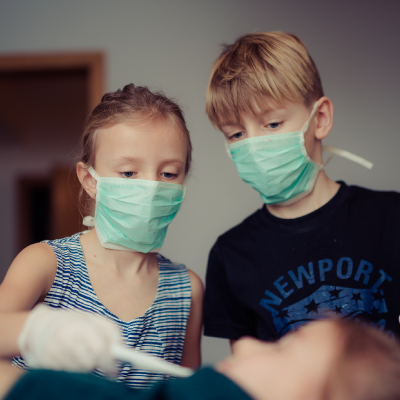 Children playing doctors with another child
