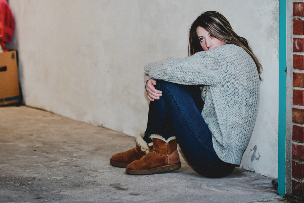 Young girl looking scared with head in knees leaning against garage wall