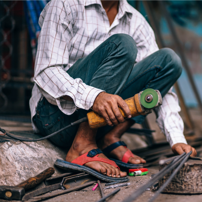 Indian man crouching on street with disc cutter to cut metal bar