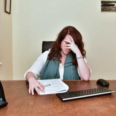 Lady sat at desk, head in hand looking stressed