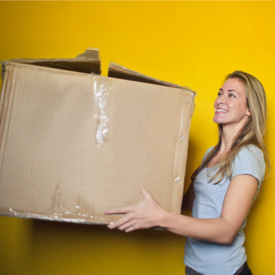 Lady holding a very large box at chest height with arms bent