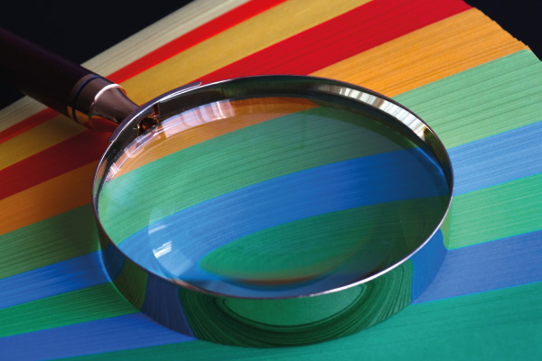 Magnifying glass resting on the end of coloured paper
