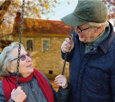 Older man looking at older lady on swing