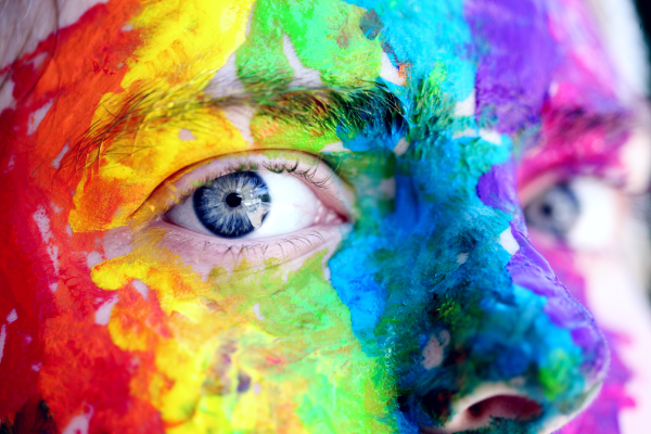 Part of face showing eyes with rainbow paint over face