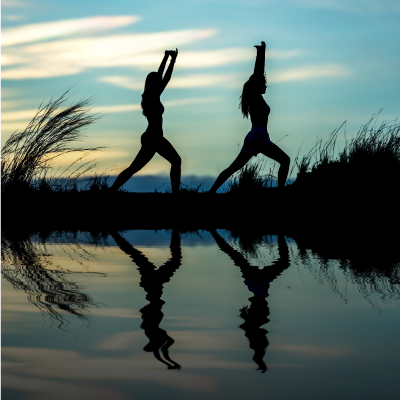 Two ladies in yoga pose by lake