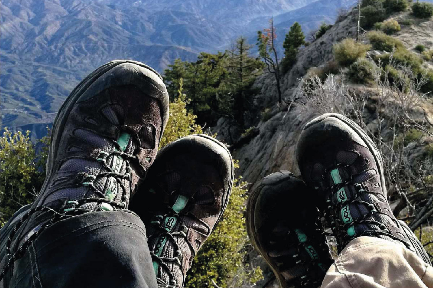 Two people wearing hiking boots sitting on top of a mountain